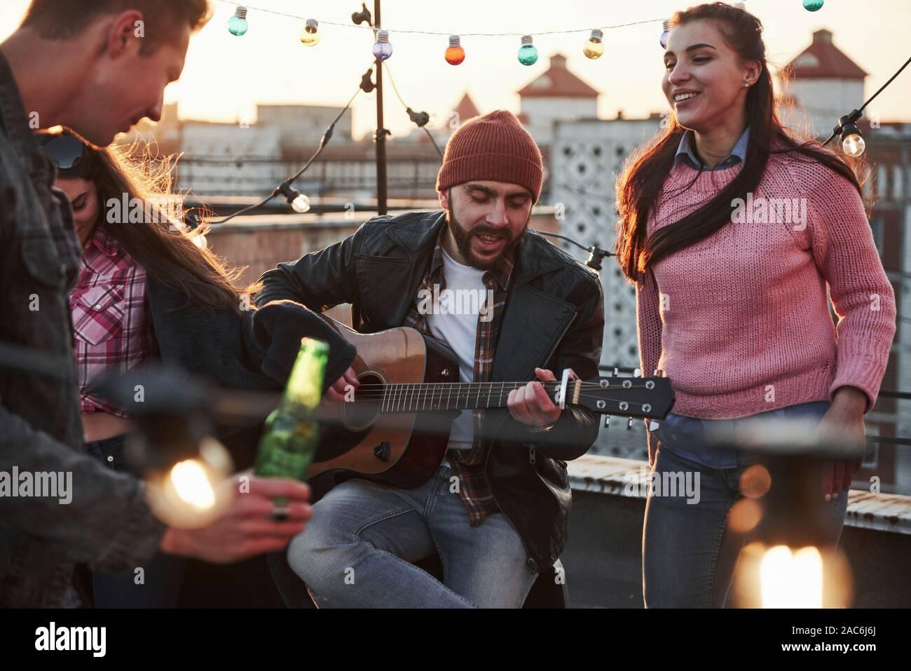 Jugar en el instrumento musical es siempre bueno tener habilidades. El guitarrista se sienta y cantando para sus amigos en la azotea con luz coloreada decorativos Foto de stock