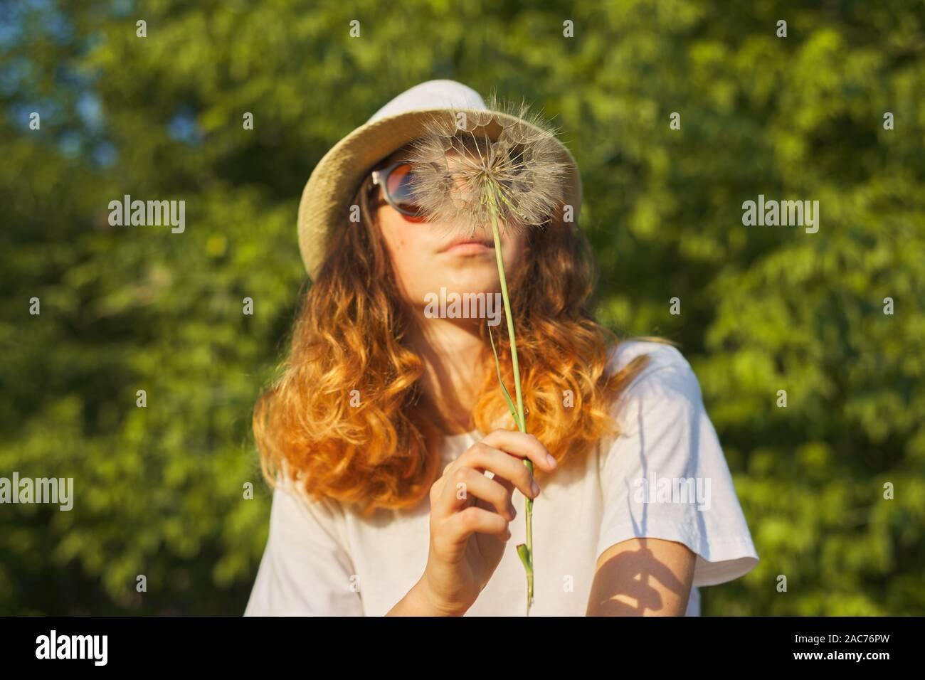 De verano al aire libre retrato de una adolescente romántica en el sombrero con grandes y esponjosas jaramago en la naturaleza, soplando sobre el diente de león en seco Foto de stock