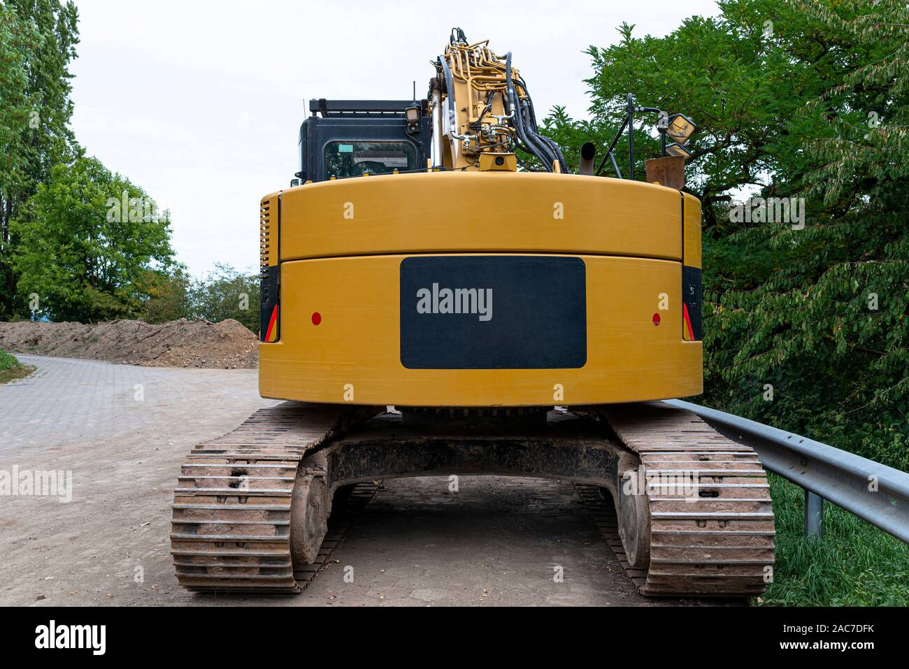Una gran excavadora amarilla visible desde la parte trasera, de pie en el cemento. Foto de stock