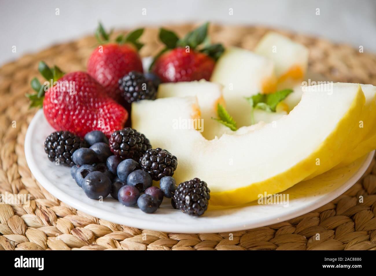 Melón cortado y bayas. Ensalada de frutas de fresas, arándanos, melón, menta y moras. Dieta ensalada en la placa blanca - desayuno, pérdida de peso. Foto de stock