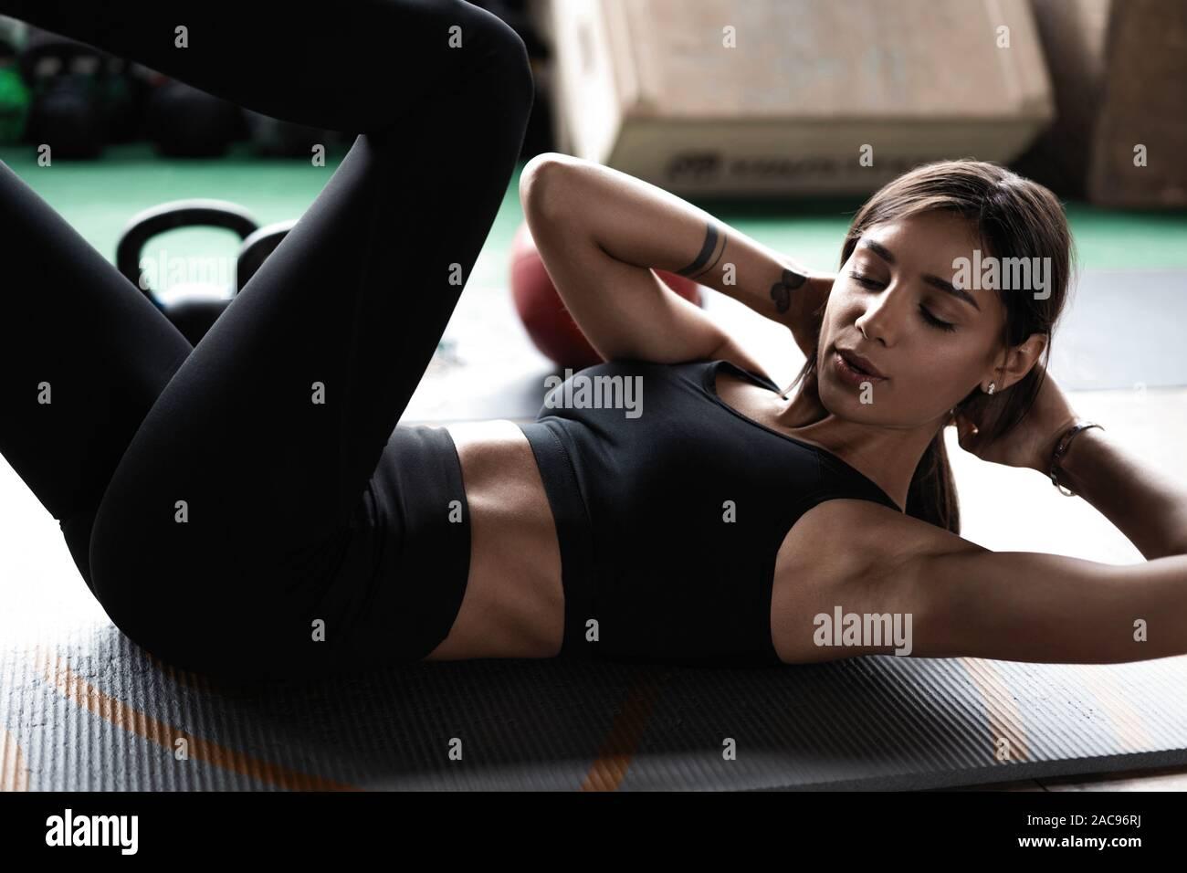 Deportes mujer haciendo bicicleta crunch entrenar en el gimnasio. Hembra en el gimnasio haciendo ejercicios de ABS de ejercicio en el gimnasio. Foto de stock