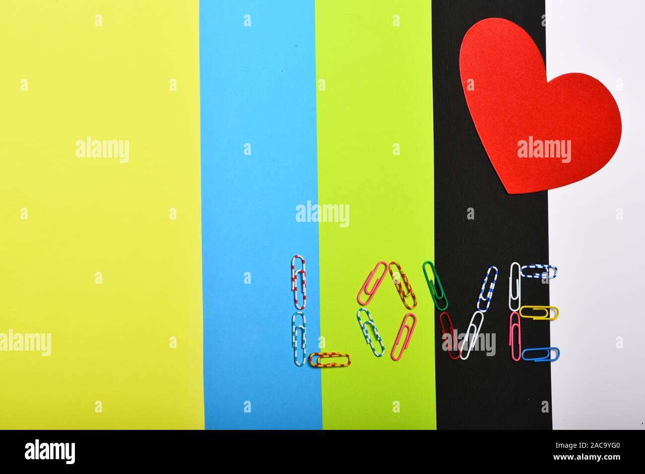 Corazón de papel rojo sobre fondo de colores, vista superior. El amor y el concepto de relación. Tarjeta del Día de San Valentín con espacio de copia. Colorido clips de papel formando la palabra AMOR. Foto de stock