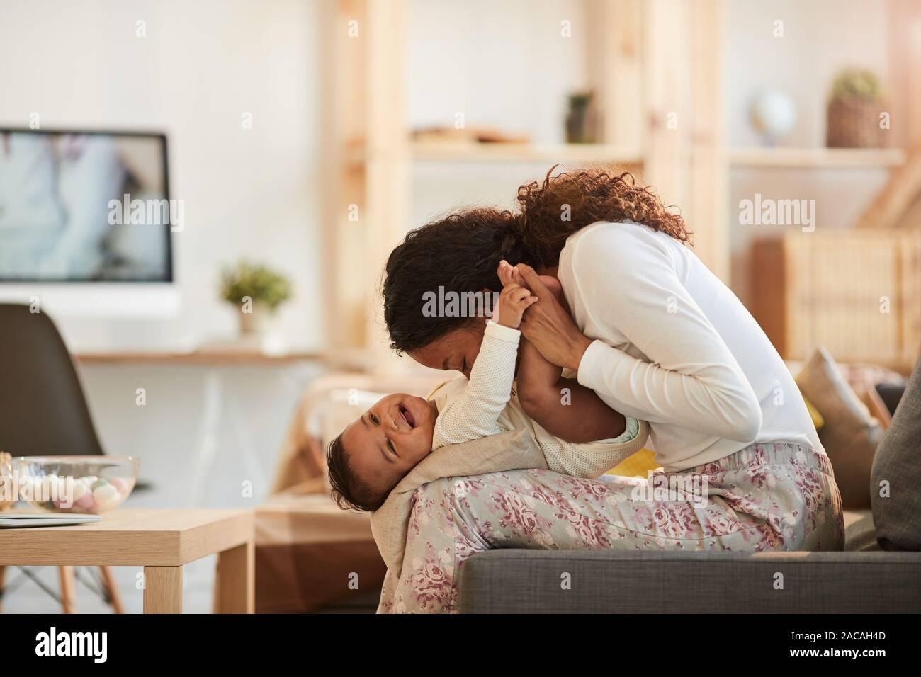 Vista lateral retrato de cuidado madre Afro-Americana besar cute Baby Boy mientras juega en casa, espacio de copia Foto de stock