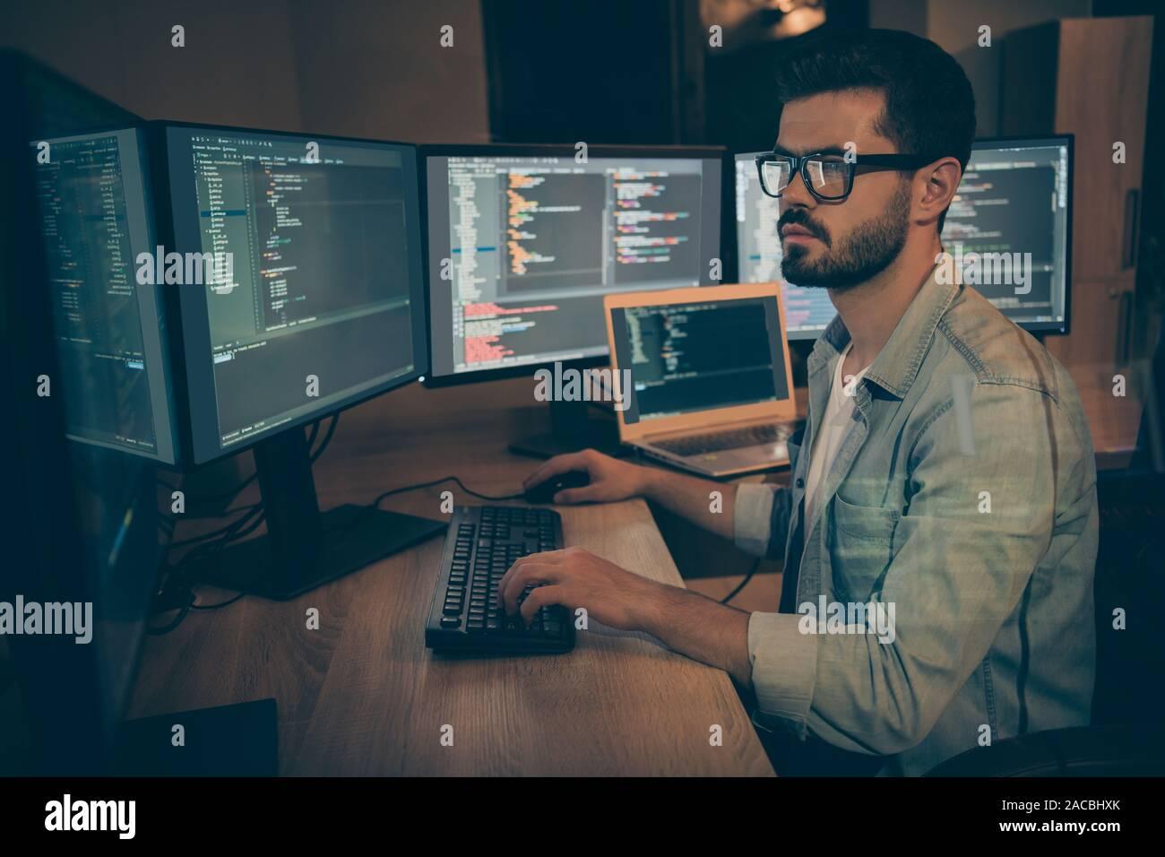 Foto de graves administrador responsable para la seguridad cibernética de gran corporación buscando brechas de seguridad existia la depuración de sistema operativo Foto de stock