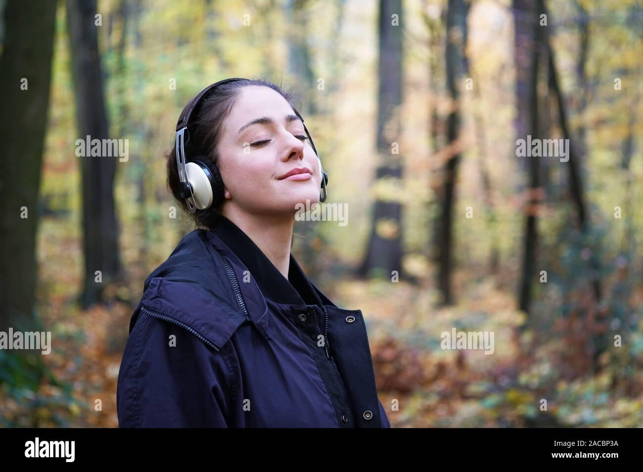 Mujer joven en su 20s al escuchar música con auriculares inalámbricos en franca forest - estilo de vida al aire libre en otoño, con espacio de copia Foto de stock