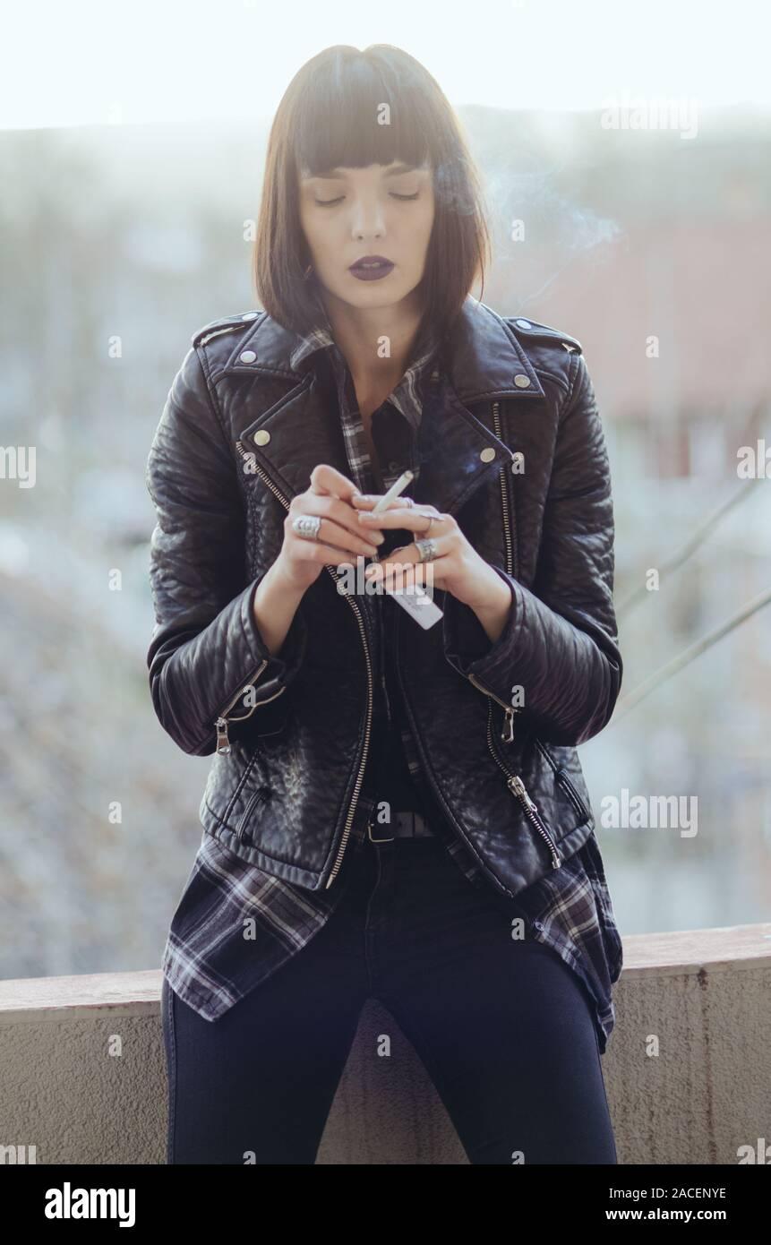 Retrato de una mujer joven con chaqueta de rock fumar cigarrillos. Foto de stock
