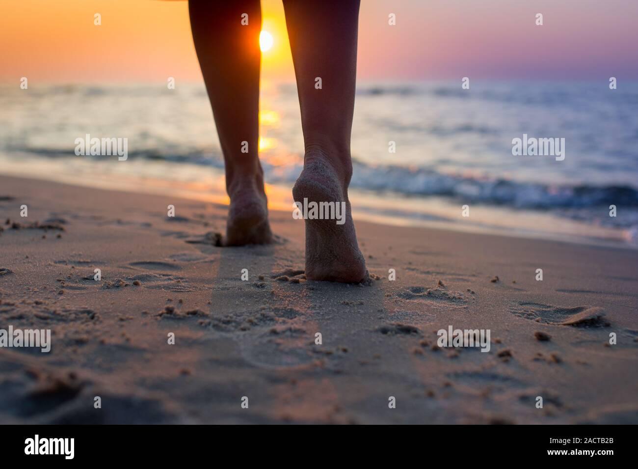 Primer plano de la mujer pies caminando por la playa durante una colorida puesta de sol. Mujer caminando hacia el mar, la parte del cuerpo, las piernas de las mujeres perfectas, disfrutar del tiempo Foto de stock