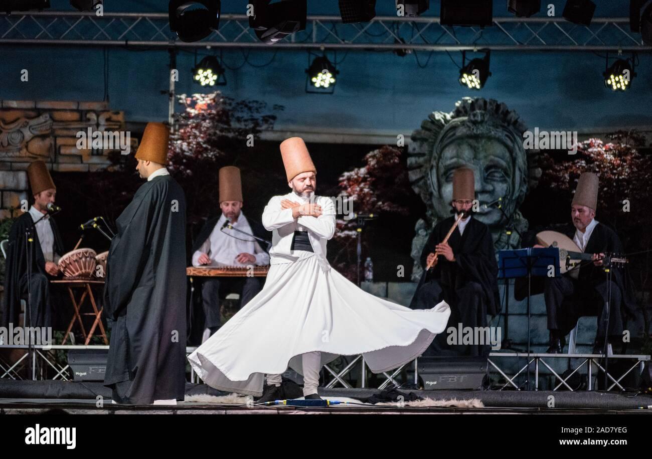 El torbellino turco bailarines o torbellino Sufi bailarines realizando de los Mevlevi derviches sema (giros) en el festival lo SPIRITO DEL PIANETA Foto de stock