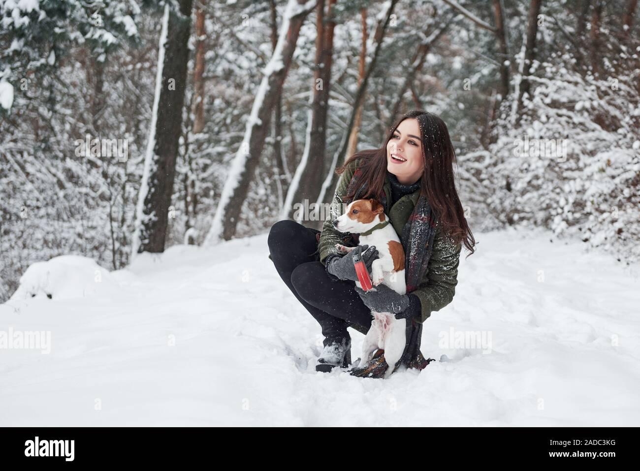 Donde debemos ir. Morena sonriente divertirse paseando con su perro en el Winter Park Foto de stock