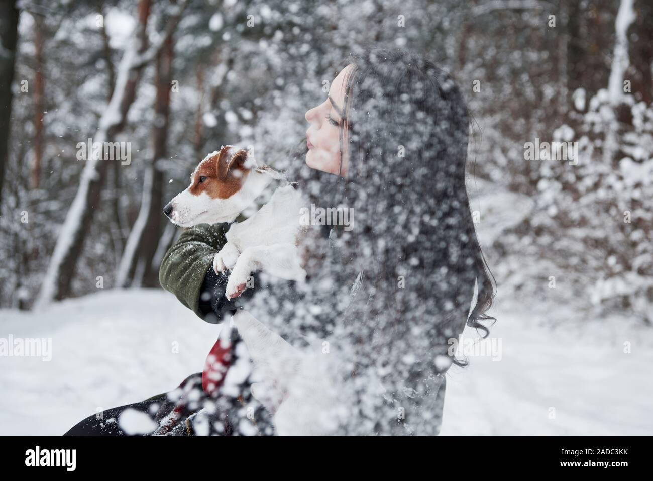 Es nieve. Morena sonriente divertirse paseando con su perro en el Winter Park Foto de stock