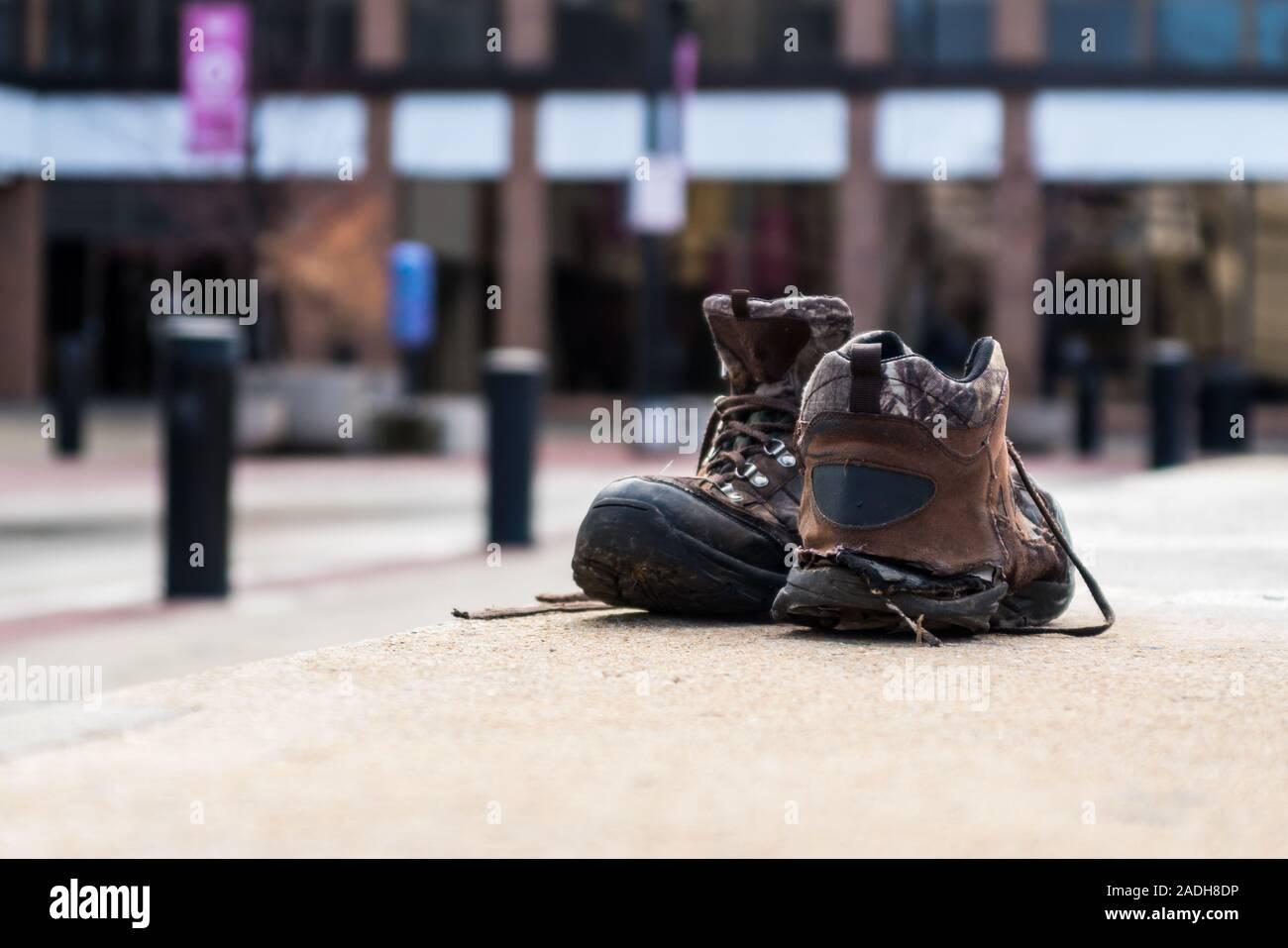 Un diseño vertical de un par de viejas botas de trabajo zapatos desgastados sentado en un muro de hormigón. Foto de stock