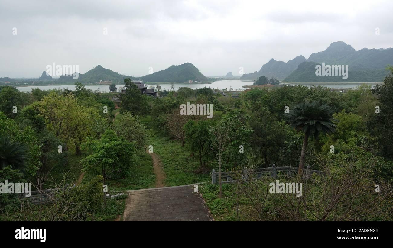 Una vista de árboles y montañas desde Bai Dinh templo espiritual y cultural complejo cerca de Ninh Binh Vietnam Foto de stock