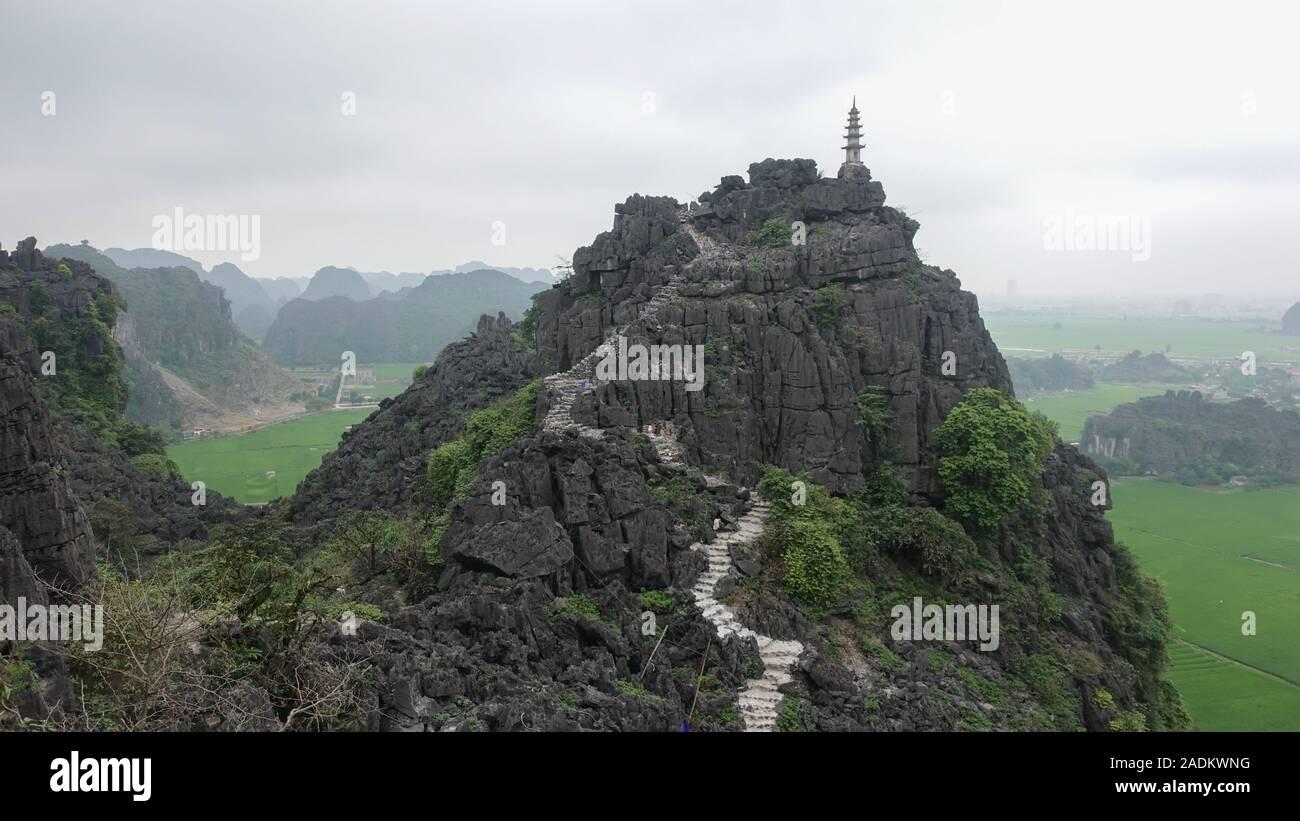 Una vista del pico de una montaña y un camino a la cumbre en el bello paisaje de Tam Coc, Ninh Binh, Vietnam Foto de stock