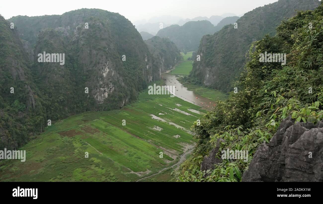 Vista de un río en un valle entre montañas gigantes en Tam Coc, Ninh Binh, Vietnam Foto de stock