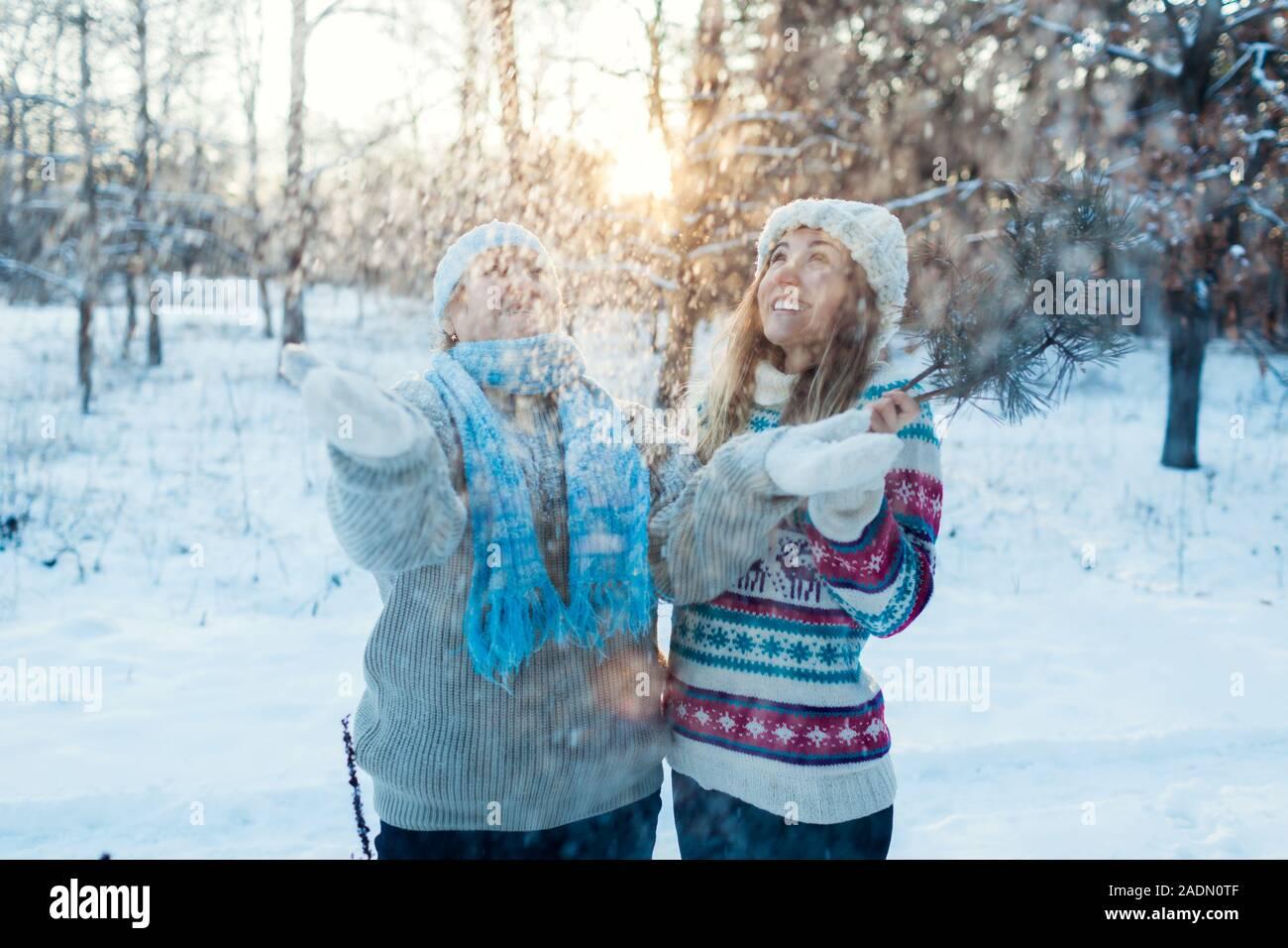 Divertidas actividades de invierno. Madre e hija adulta arrojar nieve afuera. Familia relajante en el bosque para vacaciones Foto de stock