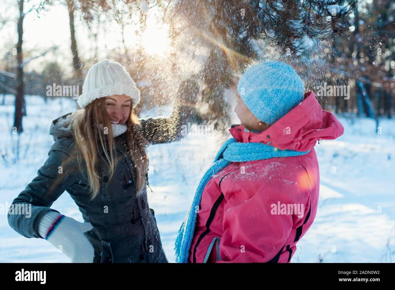 Divertidas actividades de invierno. Madre e hija adulta agitando ramas con nieve afuera. Familia de vacaciones relajantes Foto de stock