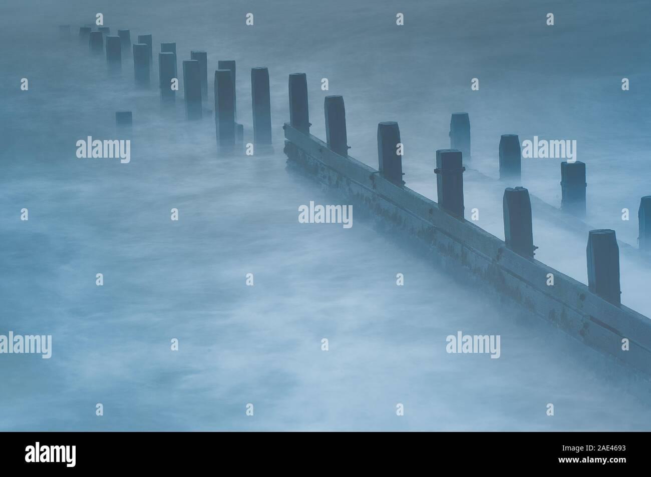 La larga exposición de las olas rompiendo sobre una ola de madera romper capeado puestos ofreciendo una línea líder en el mar del Norte. Concepto costera pacífica Foto de stock
