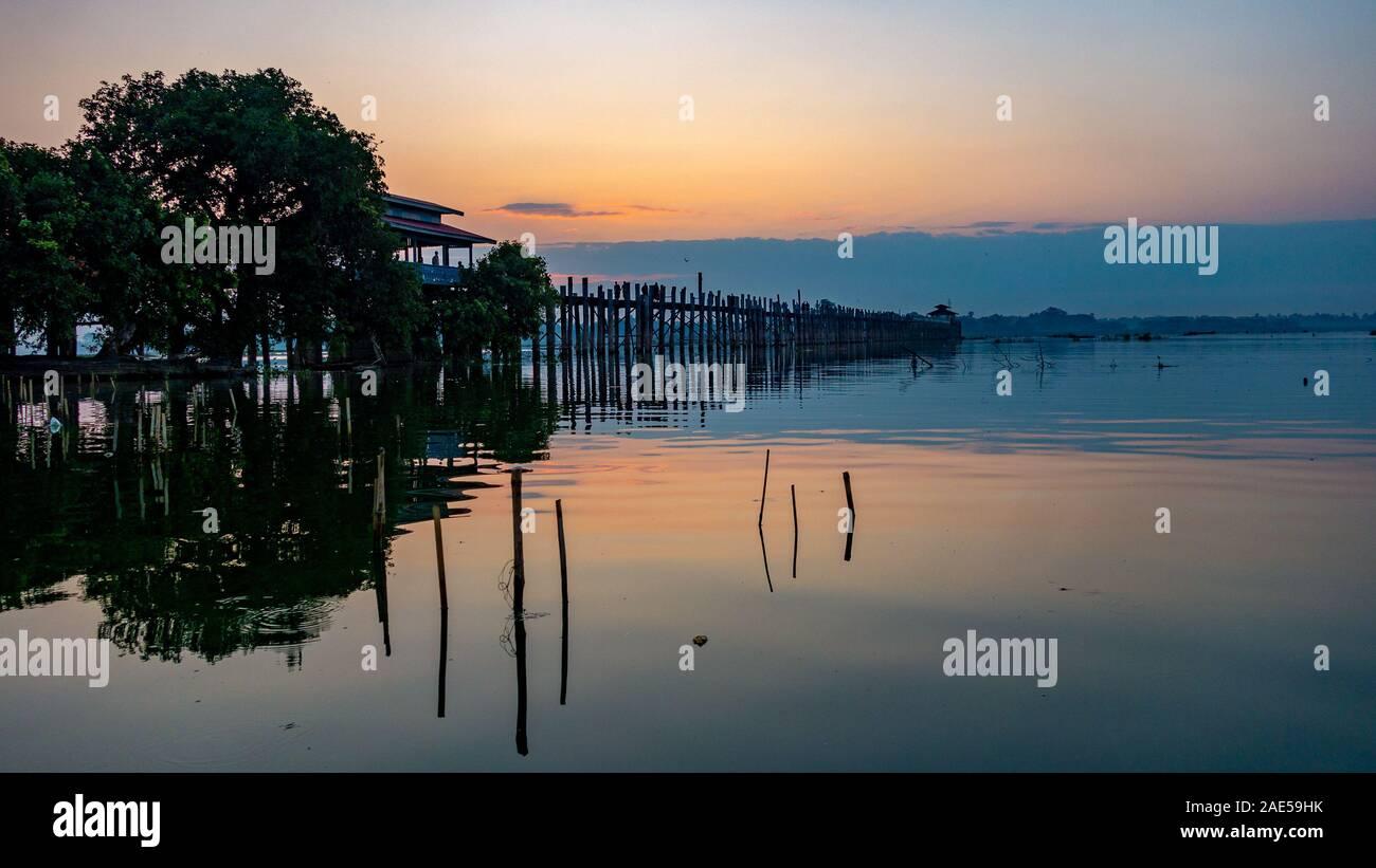 Vista del amanecer de los antiguos de madera de teca, U Bein Puente que cruza el lago Taungthaman en Amarapura, cerca de la ciudad de Mandalay en Myanmar (antigua Birmania) llamado Foto de stock