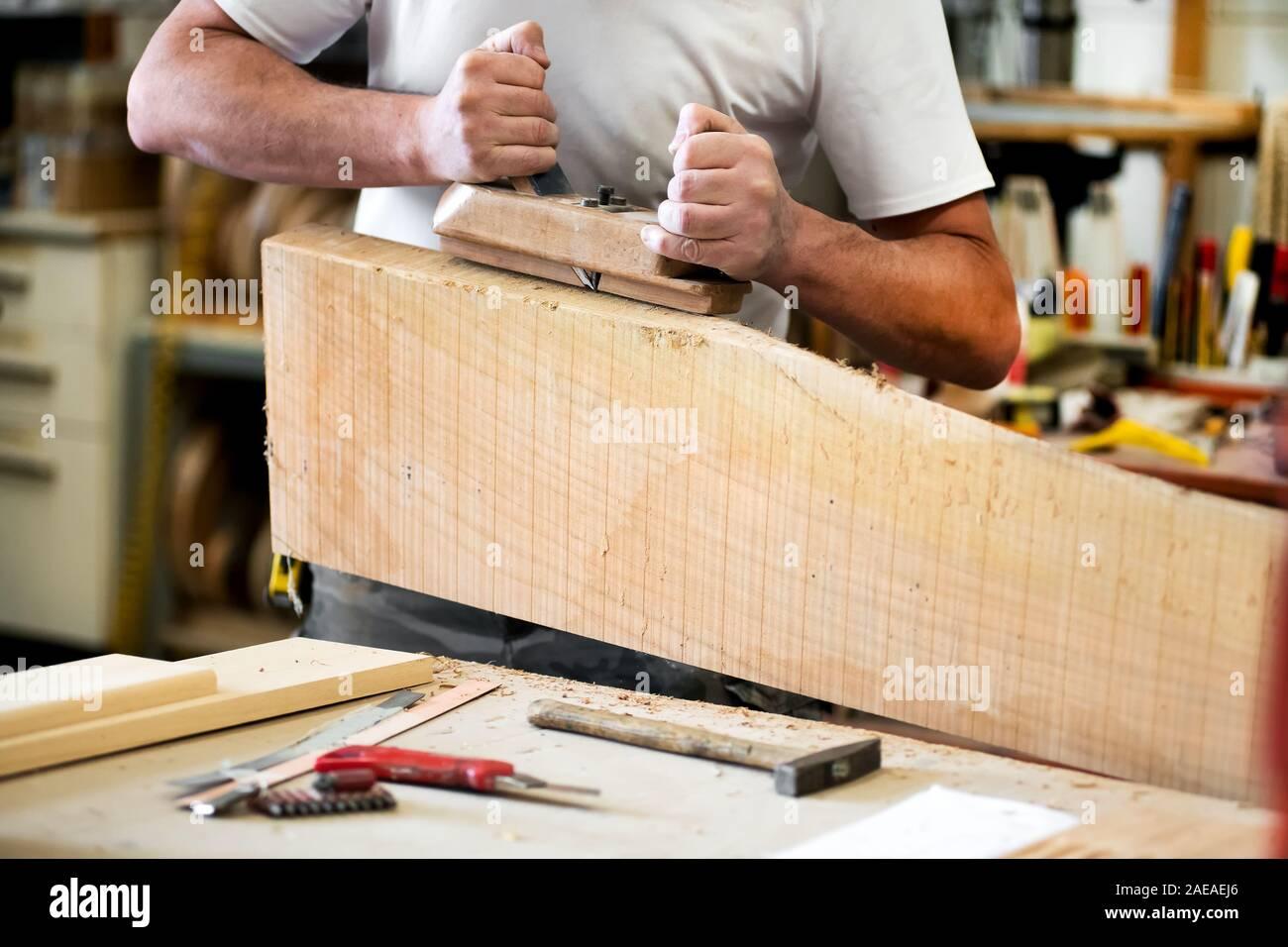Carpenter trabaja con un planeador en un bloque de madera alisando la superficie en un primer plano de sus manos y herramientas sobre el workbench Foto de stock