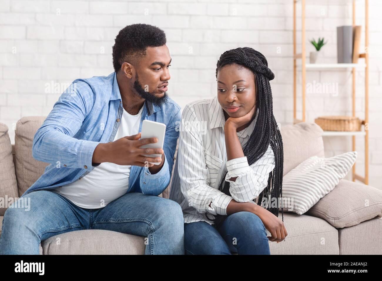 Novio celoso mostrando su novia engañando a su teléfono, exigiendo explicación Foto de stock