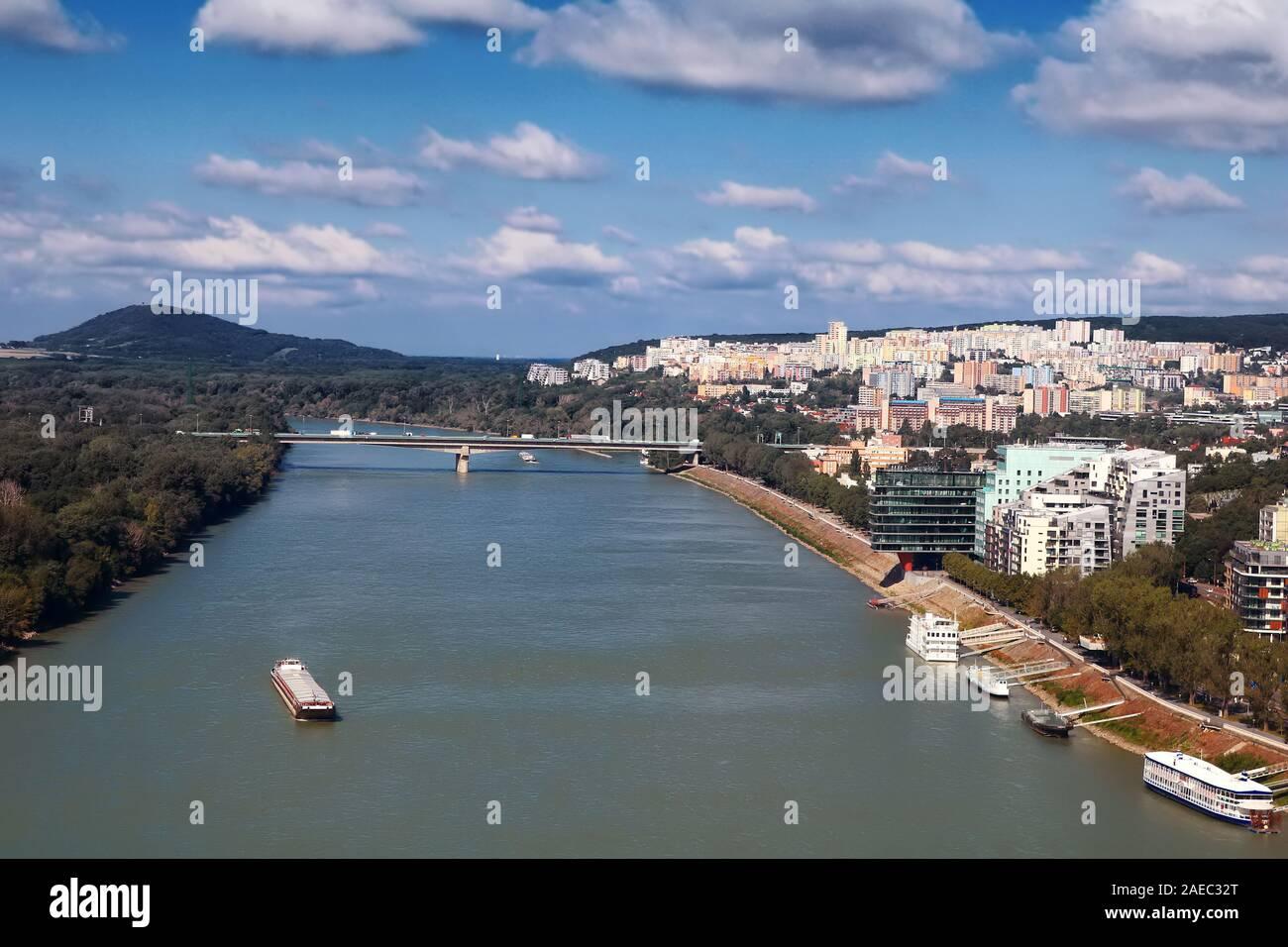 Vista del barco en el río Danubio, el puente Lafranconi y los edificios de nueva construcción en una zona residencial en Bratislava, Eslovaquia Foto de stock