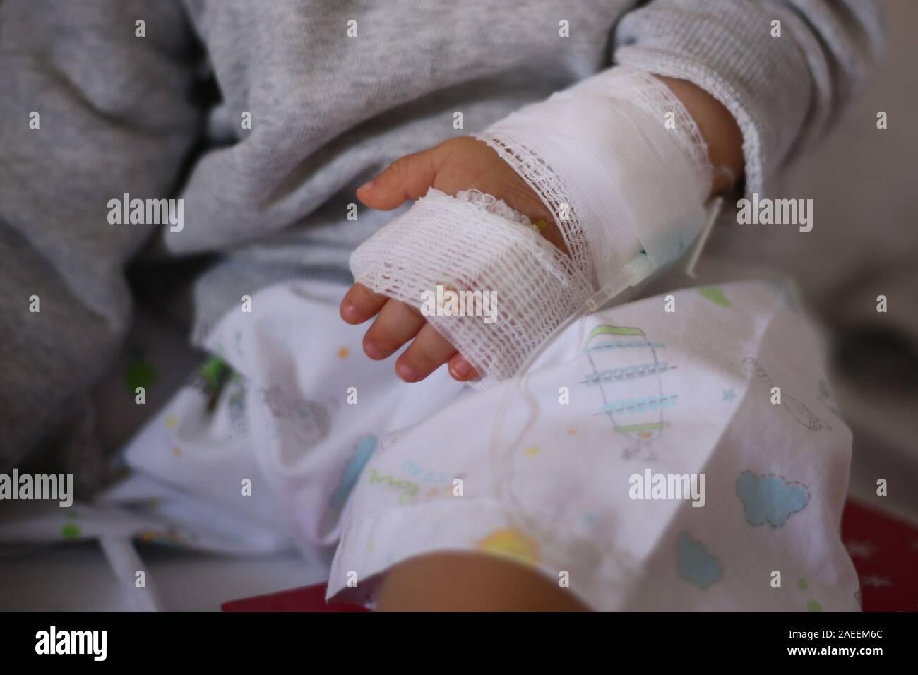 Infusión salina. enfermedad del bebé hacia adentro paciente sentado en las piernas de padres. El bebé en el hospital alimentándose. enfermos cabrito en proceso de tratamiento, en el hospital y el cuidado por Foto de stock