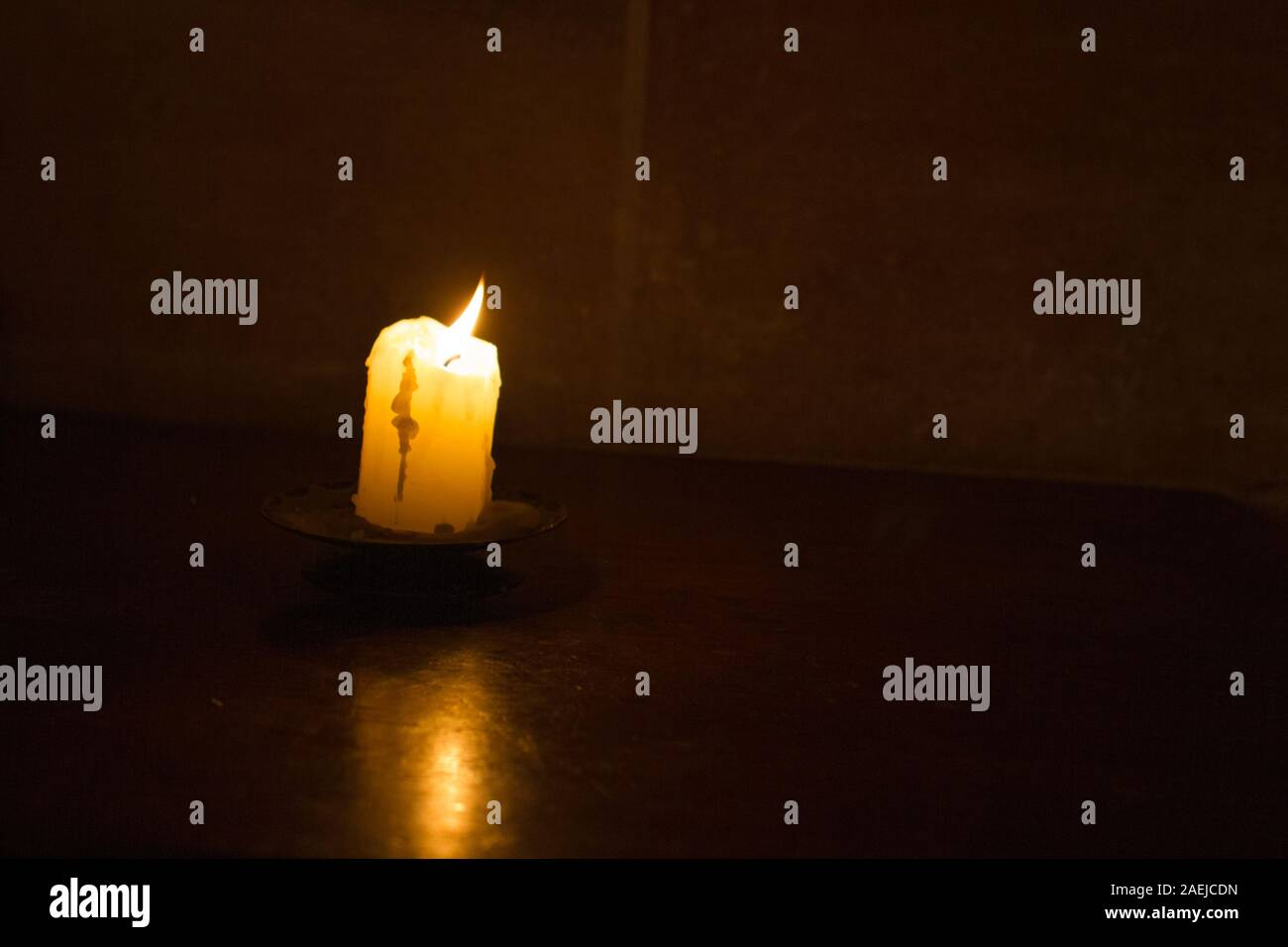 Solo velas encendidas en una iglesia aislada contra la oscuridad y una pared oscura como símbolo de creencia, religión, cristianismo Foto de stock