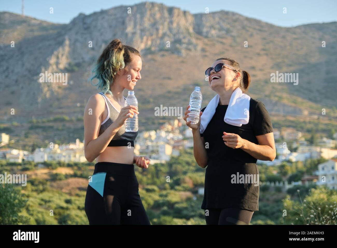 Madre e hija hablar y beber agua después de entrenar Foto de stock