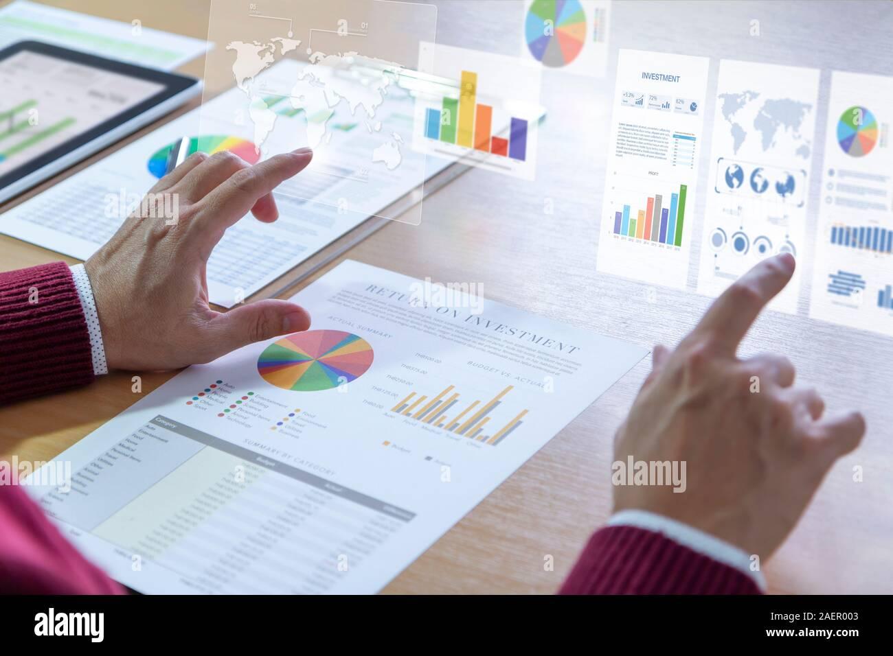 Empresario interactúa con gráficos de realidad aumentada mientras profundamente revisando un informe financiero para un retorno de la inversión o el análisis de riesgo de inversión Foto de stock