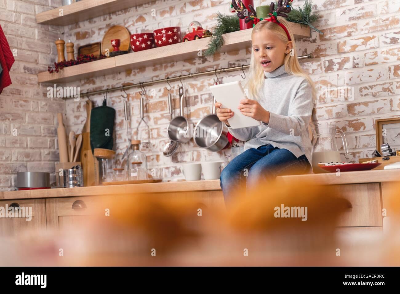 Poco caucásico niña jugando juegos en línea en interiores Foto de stock