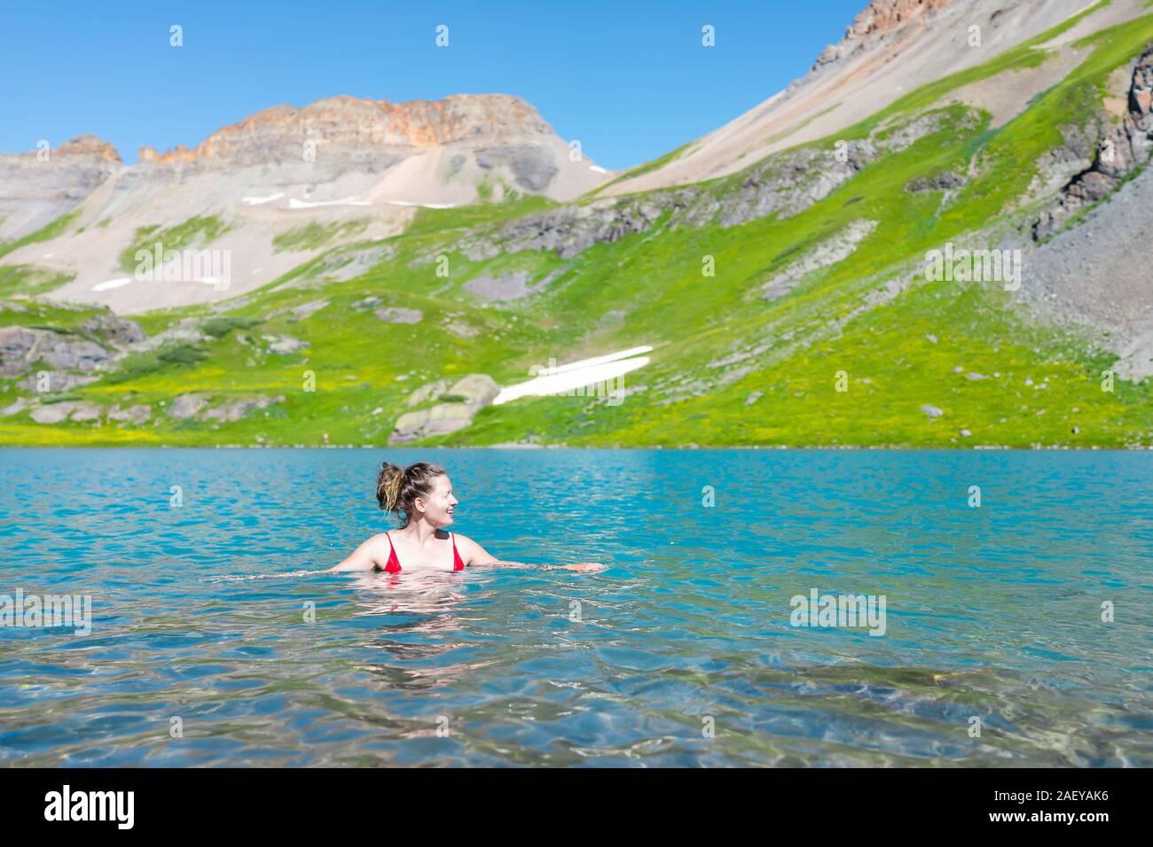 Joven Mujer feliz chica nadando en agua fría de hielo del lago vibrante en el famoso sendero en Silverton, Colorado en San Juan la montaña en verano Foto de stock