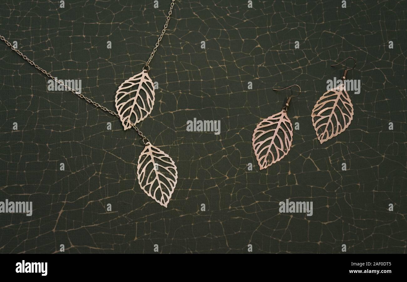 Juego de accesorios de oro inspirado en la naturaleza. Chica Collar y aretes par sobre fondo verde agrietada Foto de stock