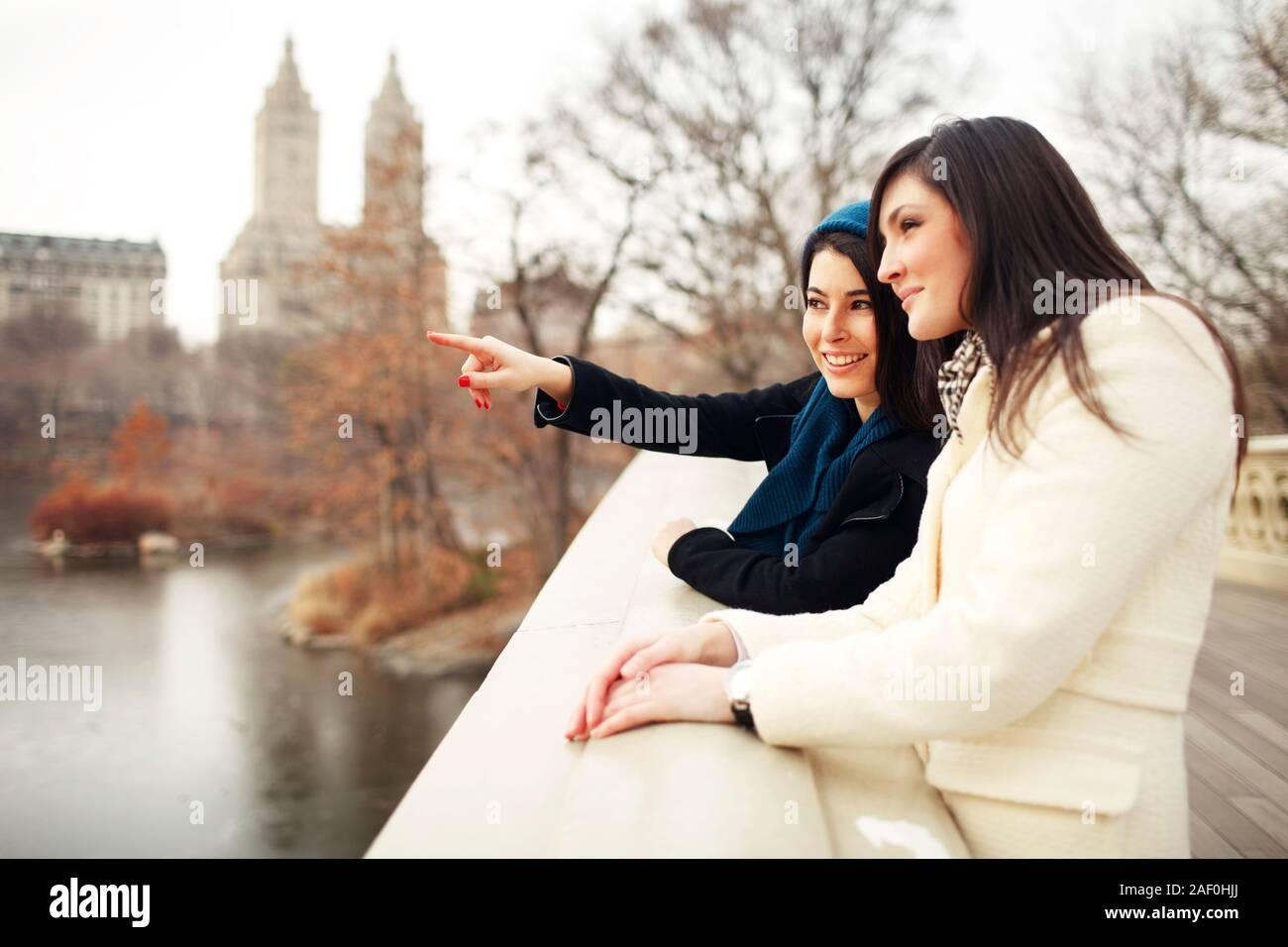 Mujer señalando a la distancia con un amigo, en las cercanías del parque de la ciudad Foto de stock
