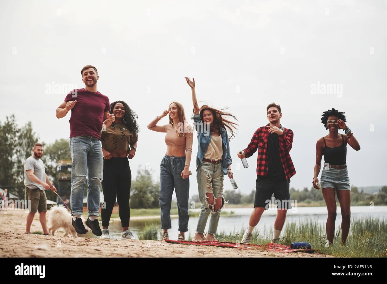 Hombre con perro blanco está caminando detrás. Grupo de personas tienen un picnic en la playa. Amigos divertirse en horario de fin de semana Foto de stock