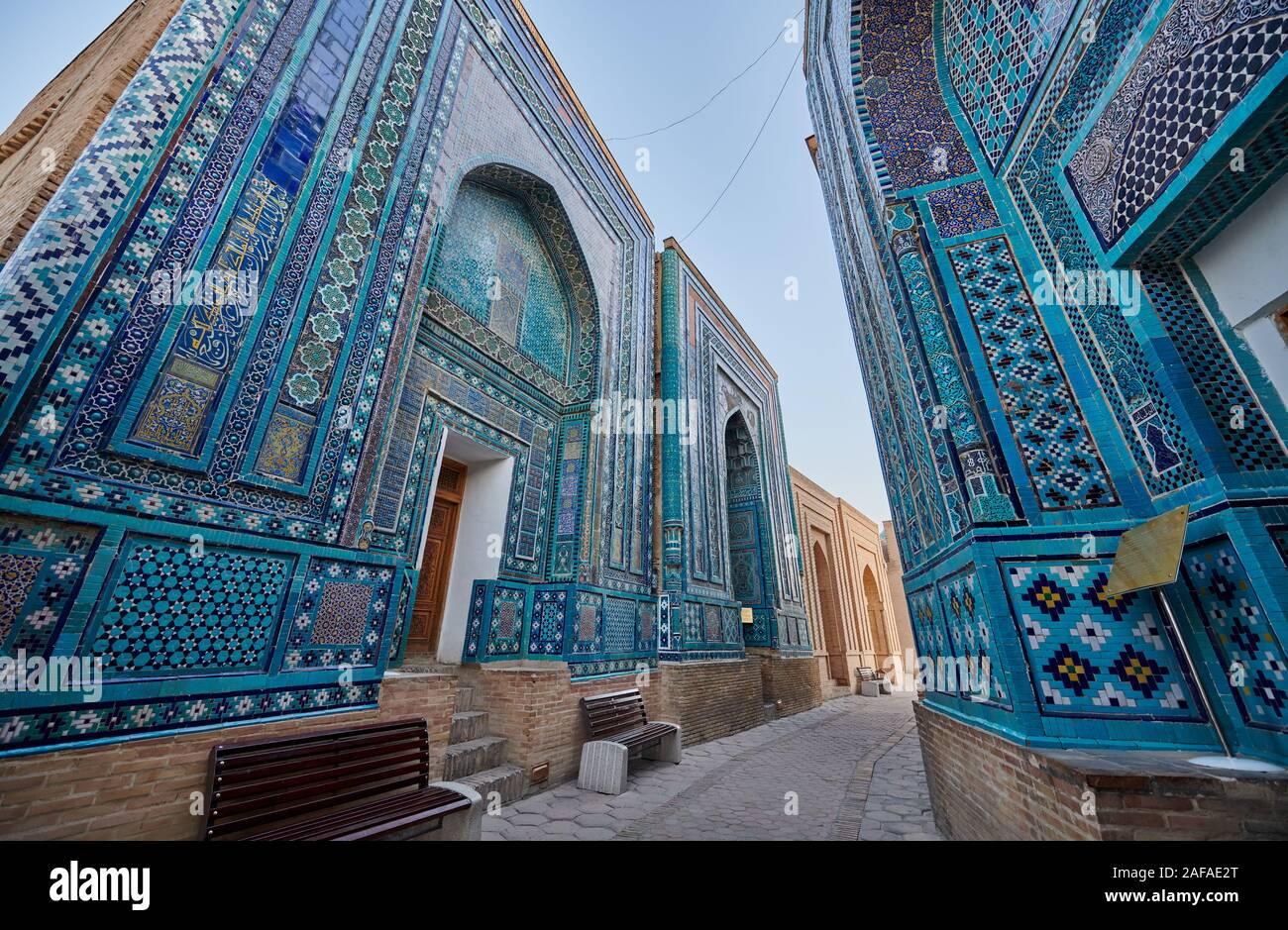 Estrecho camino a través de las fachadas profusamente decorados con azulejos azules en necrópolis Shah-i-Zinda, Samarqand, Uzbekistán, en Asia Central Foto de stock