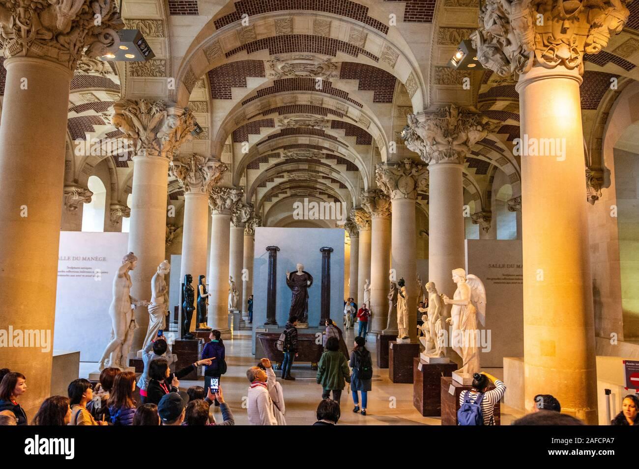 Interior del Museo del Louvre en París con la gente de la ciudad y visitantes caminar y tomar fotos Foto de stock