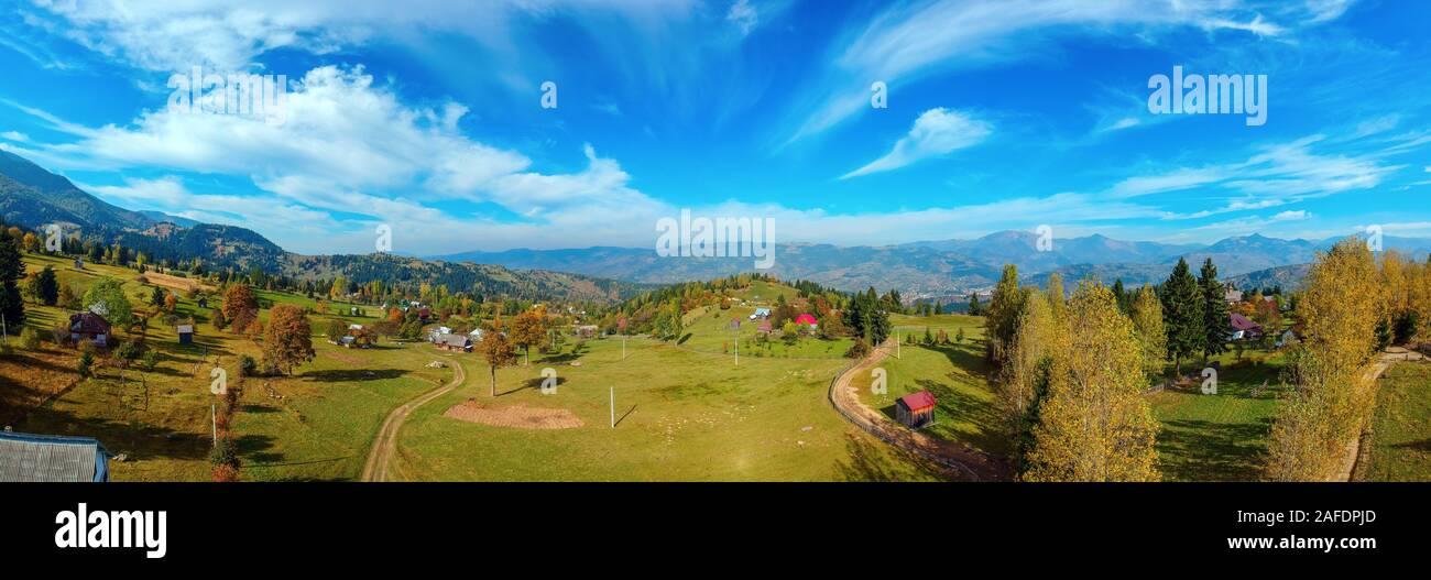 Vistas panorámicas aéreas de una región rural con granjas, campos y la cordillera de los Cárpatos en el fondo en un soleado día de otoño. Borsa, Maramu Foto de stock