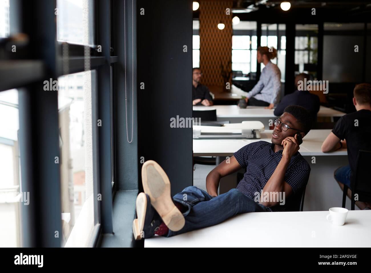Jóvenes creativos macho negro sentado en una oficina con sus pies sobre el escritorio con teléfono, cerrar Foto de stock