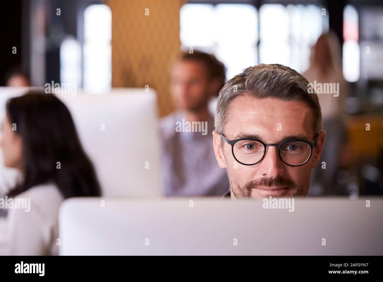 De mediana edad, blanco, masculino creativo usando un ordenador en una oficina ajetreada, el enfoque selectivo, cerrar Foto de stock