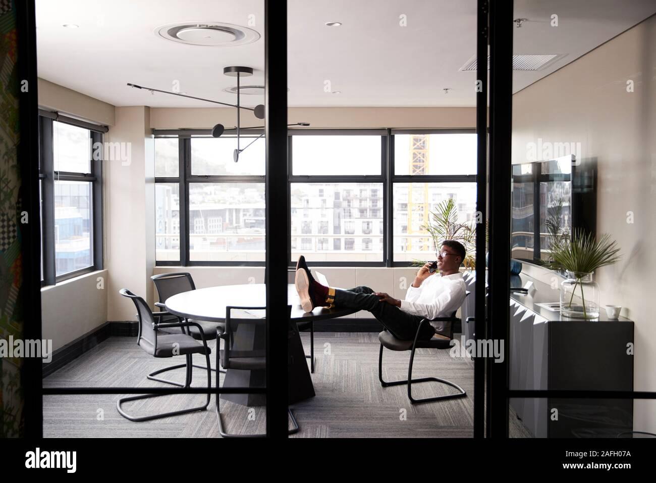 Empresario negro milenario hablando por teléfono con los pies para arriba en un escritorio, visto desde la puerta Foto de stock