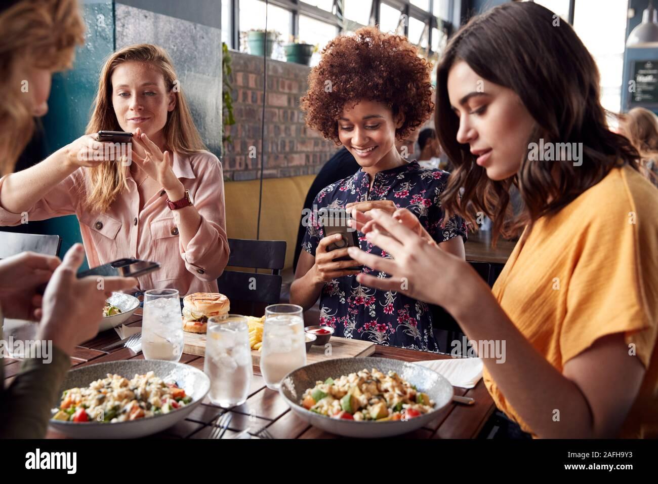 Amigas en el restaurante tomar la foto de la comida en el restaurante para publicar en los Medios de Comunicación Social Foto de stock
