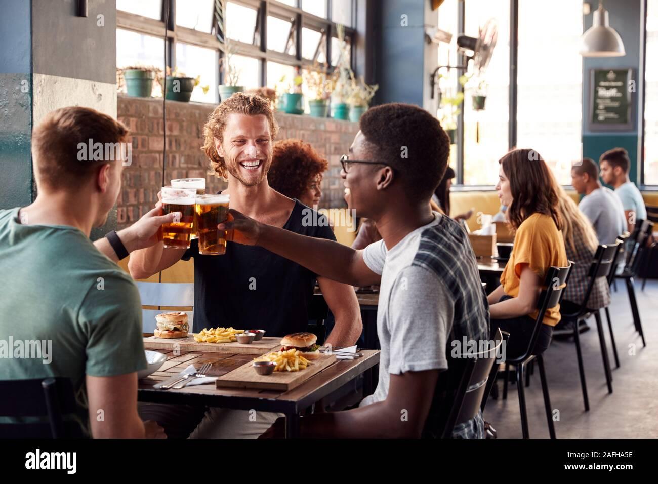 Tres jóvenes amigos varones reunión de bebidas y alimentos para hacer un brindis en el restaurante Foto de stock