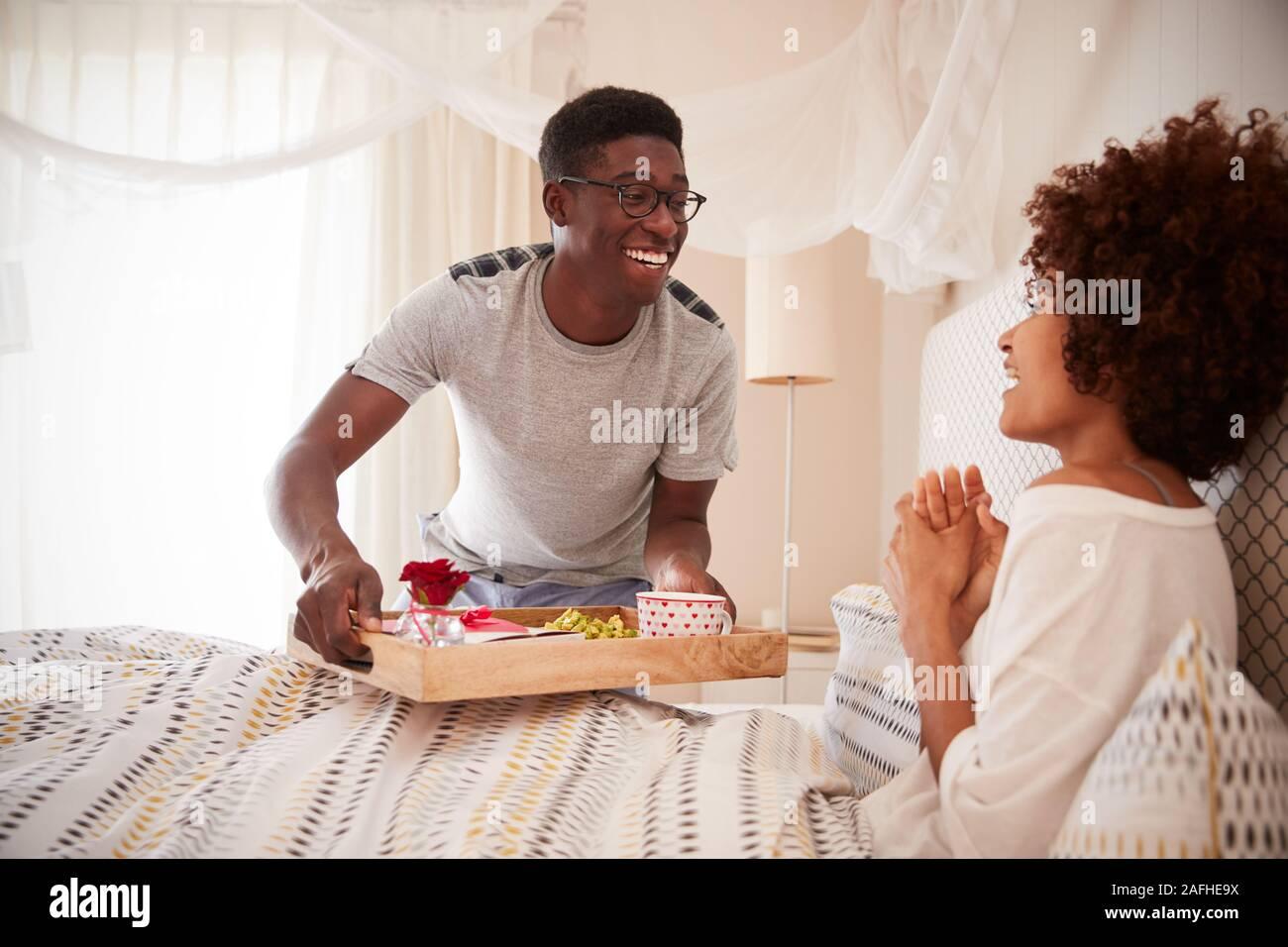 Pareja de Americanos Africanos milenario celebrando, el hombre llevando a su compañero el desayuno en la cama, cerrar Foto de stock