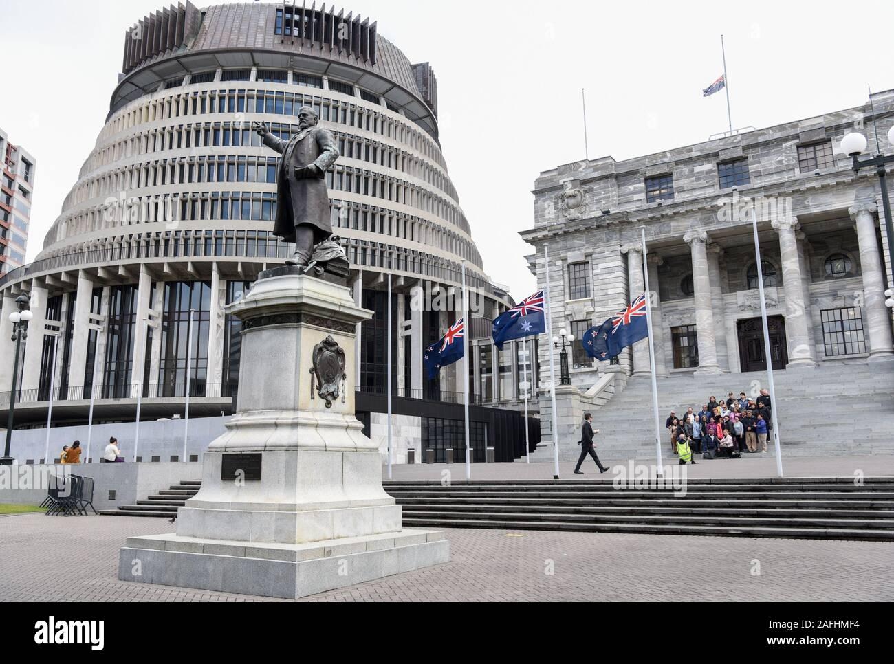 Wellington, Nueva Zelanda. 16 dic, 2019. Los nacionales de Nueva Zelanda banderas a media asta en frente de los edificios del parlamento para conmemorar a las víctimas de la erupción volcánica de la Isla Blanca en Wellington, Nueva Zelandia, el 16 de diciembre, 2019. Es necesario hacer preguntas y responder respecto a las bajas causadas por la erupción volcánica de la Isla Blanca, dijo el Primer Ministro de Nueva Zelandia Jacinda Ardern en lunes. Gente de toda Nueva Zelanda observaron un minuto de silencio el lunes en honor de las víctimas de la erupción volcánica de la Isla Blanca. Crédito: Guo Lei/Xinhua/Alamy Live News Foto de stock