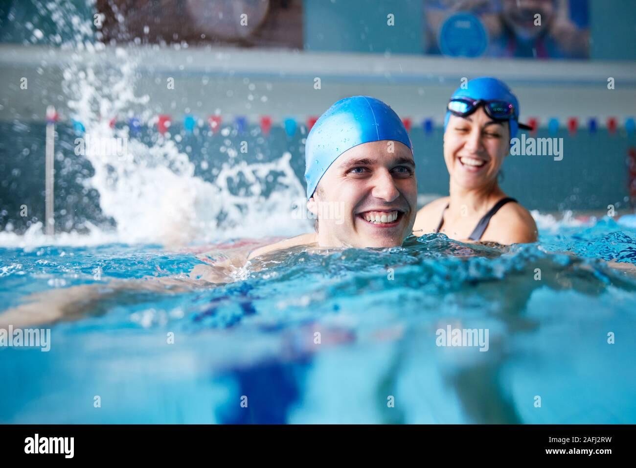 Profesor de natación femenino hombre dando lecciones Uno a uno en la piscina Foto de stock