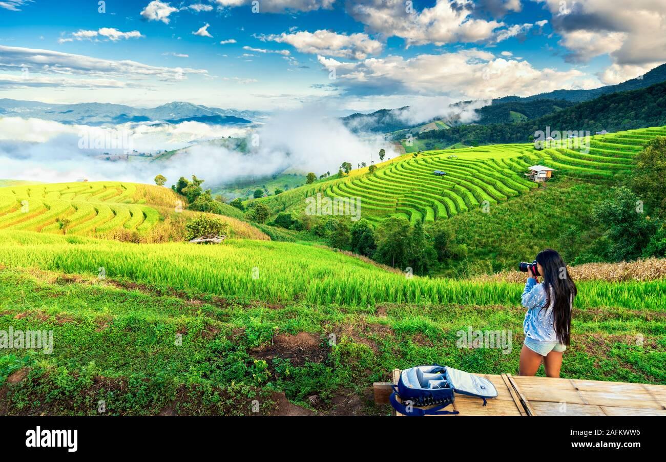La chica del viajero hace foto paisaje natural y disfrutar del paisaje ver la terraza de arroz en Asia al amanecer. Estilo de vida activo y concepto de viaje Foto de stock