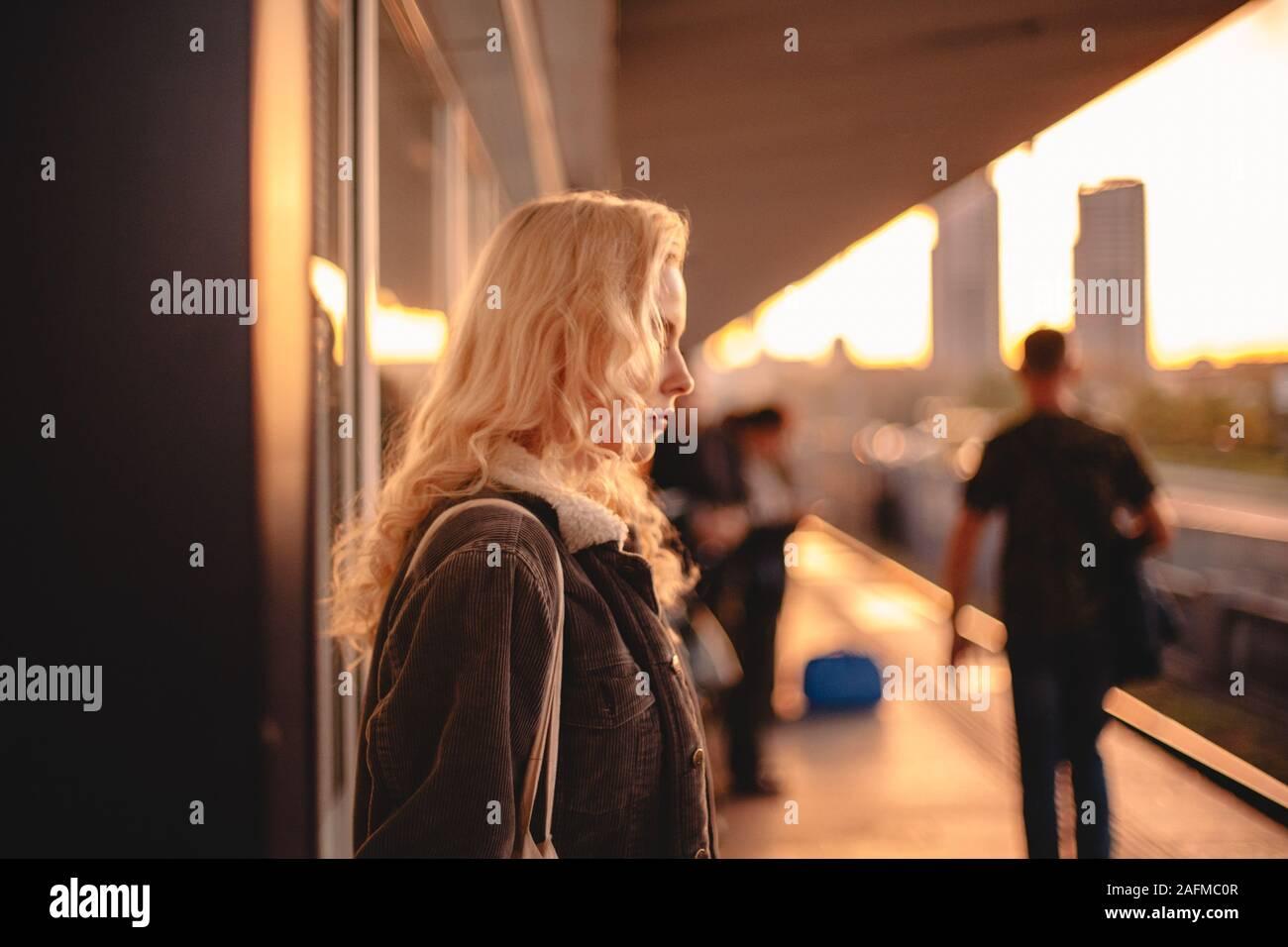 Mujer joven con cabello rubio esperando el tren en la estación de metro Foto de stock