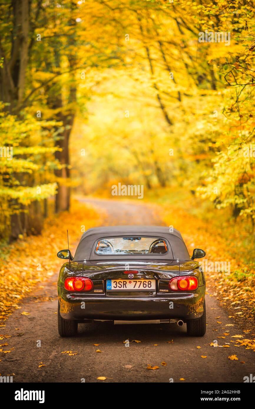 Praga, República Checa, Octubre 2019: Mazda MX-5 Miata NB de segunda generación, el modelo del año 1999 en un frondoso camino en otoño con bello otoño colorido Foto de stock