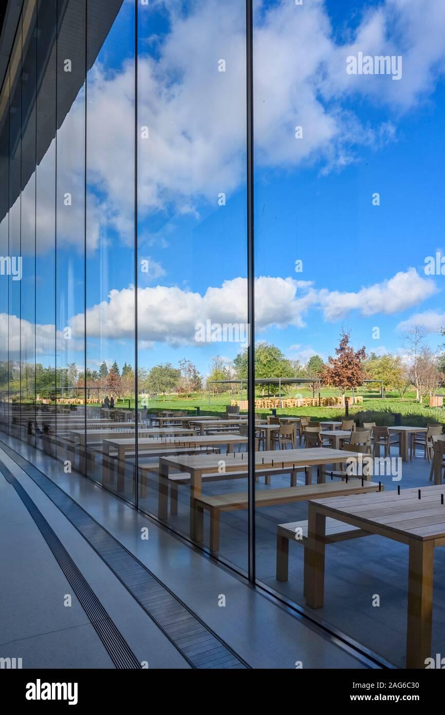 Cupertino CA EE.UU. Diciembre 14, 2019: edificio de oficinas de la sede de Apple, mirando a través de la ventana de cristal dentro de una entrada lateral a la piscina e Foto de stock