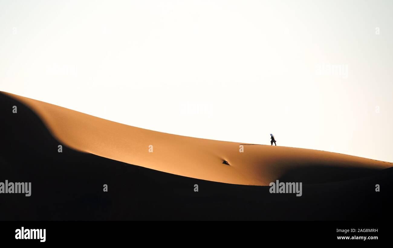 El hombre que camina sobre la duna de arena en el desierto de LUT Foto de stock